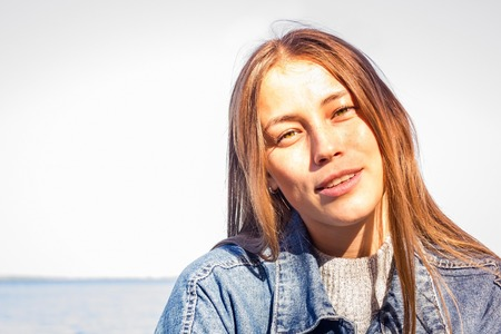 The girl with long blond hair against the backdrop of the sea landscape. Green eyes, freckles on face. Solar lighting.
