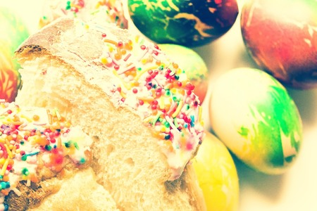Easter background, painted eggs and Easter cake. Yellow, red and green colors. Light toning, top view.