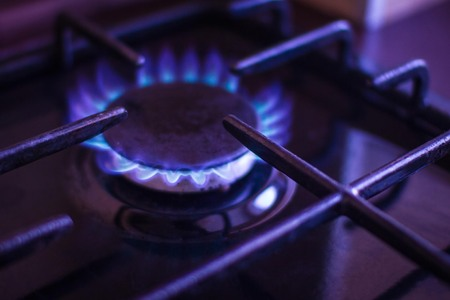 Blue flame, household gas, propane, methane. Home gas stove, the background is blurred. Violet toning.