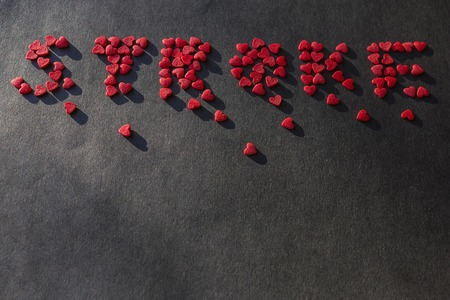 Red little hearts laid out the word stroke. Disease, illness, health problems. Dark background, copy space.