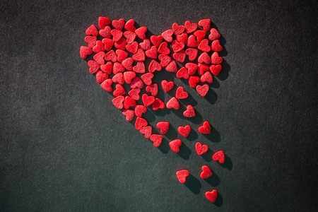 The red heart is made up of small pieces, it crumbles. Symbol of longing, unfulfilled hopes. Black background, top view.
