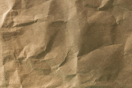 Background brown crumpled paper without pattern. Organic, eco-friendly packaging material. Side lighting.
