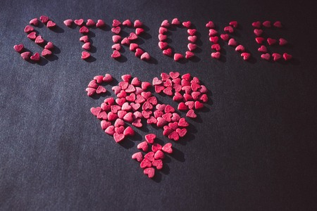 Broken heart and red inscription stroke. Heart attack, health hazard. Toning, muted colors. Stock Photo