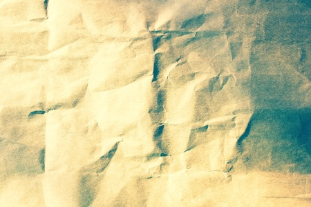 Crumpled paper, light brown and beige shades. Retro style, vintage toning. Without picture. Side lighting.