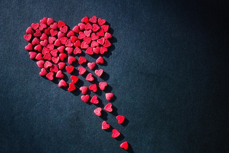 Black background, red heart crumbles into pieces. Unhappy love, love problems, parting. Side lighting, copy space.