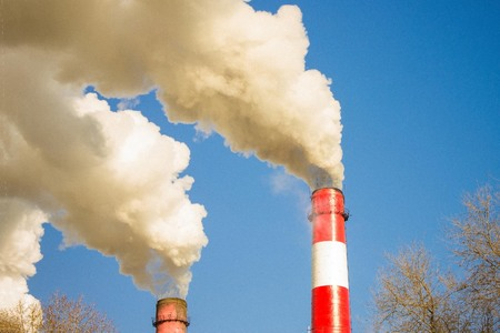 Air emissions, environmental disaster. Smoking pipes on the background of bright blue sky. Copy space.