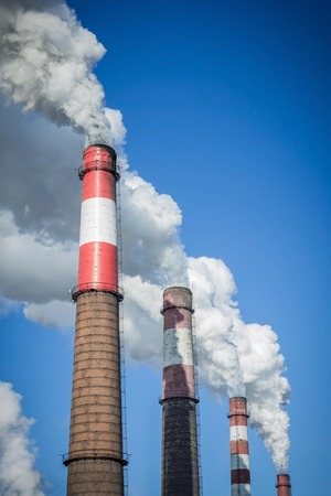 Huge factory pipes, a large enterprise. Air pollution, thick clouds of white smoke. Blue sky, copy space. Reklamní fotografie