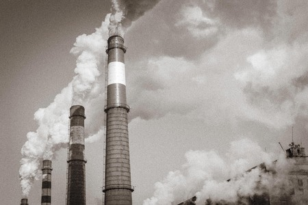Smoke comes from large pipes. Poor environmental conditions, air pollution. In black and white. Solar lighting.