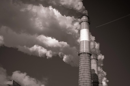 Thick smoke from industrial pipes. Ecological problems, pollution. Solar lighting. In black and white.