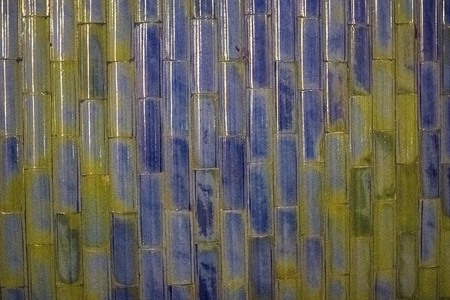 Facing, the wall is decorated with narrow colored ceramic tiles. Blue, brown, green colors, abstraction. Side lighting. Stock fotó