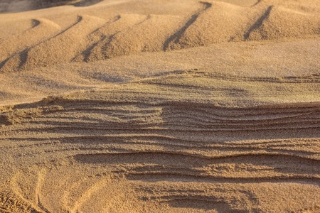 Yellow, beige sand, natural texture. Sand dunes, abstraction. Solar lighting, the background is blurred.