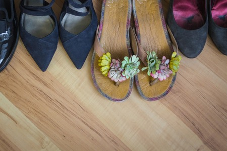 Waiting for summer, vacation, rest. Womens sandals and office shoes. Free lifestyles, downshifting. Light wooden background, top view.