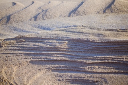 Sand, layered structure. In the background are dunes. Toning, solar lighting.