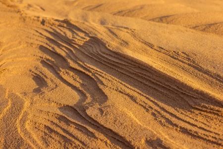 Natural texture, sand, landscape. Evening sunlight. The far plan is blurred.