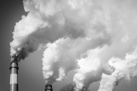 Smoking pipes against the sky. Ecological disaster, air pollution. In black and white, vignetting.