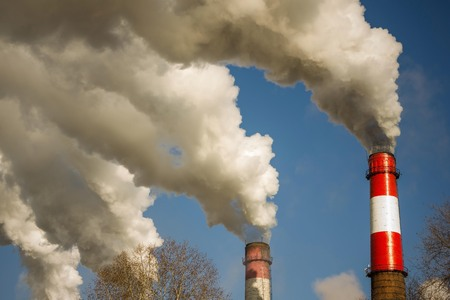 Thick white smoke against a blue sky. Industry, bad ecology, global warming. Bright sunny day.