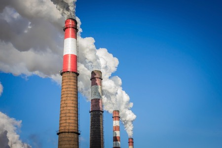 Smoking chimneys, factory, industrial plant. Bad ecology, air pollution. Bright blue sky, copy space. Imagens