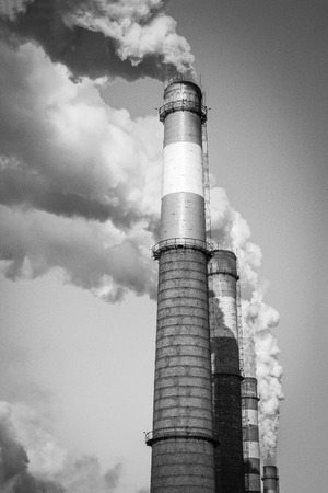 Pipes produce thick smoke into the sky. Industrial emissions, polluted air, poor environment. In black and white, vignetting.