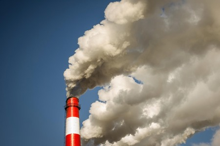 Air pollution, emissions, poor ecology. Thick clouds of smoke from a large factory chimney. Day sunlight, vignetting.