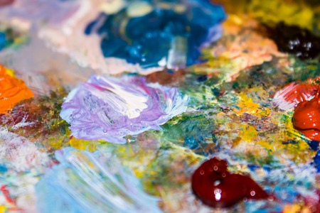 Oil paints on the palette, bright colors, mix. Abstract background, edges blurred.
