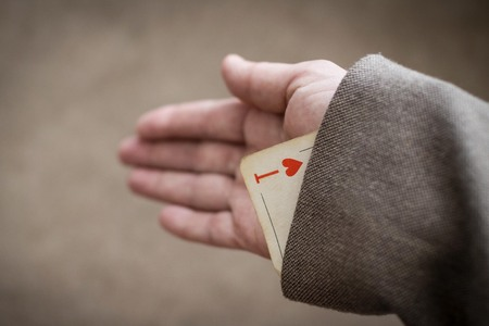 In the sleeve of his jacket hidden trump card. Unfair play, hidden features, compelling argument. In focus is a playing card, the background is blurred. Stock Photo