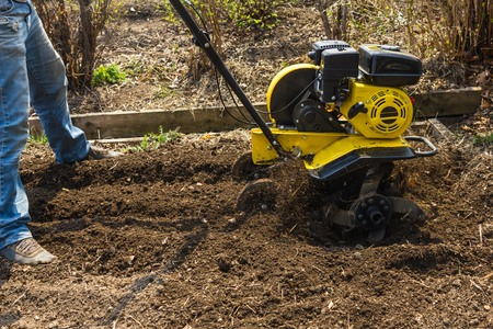 Plowing in the spring. The manual plow plows the soil. Earth, soil, brown. Daytime sunshine.
