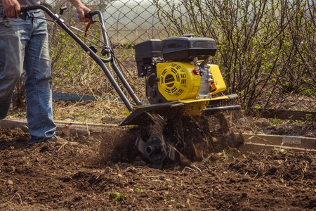 Spring plowing the land. Hand motorbike, tillage equipment. Farm, summer house, sunny day.