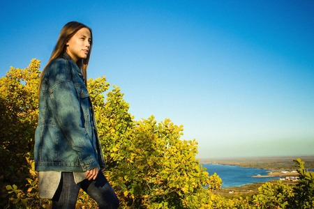 Young woman in denim clothes looks into the distance. Blue sky, green foliage, horizon line in the distance. Copy space.