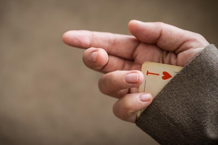 Ace in the sleeve, hidden resource reserve. Cheating, the game is not by the rules. The background is blurred, vignetting. Copy space.