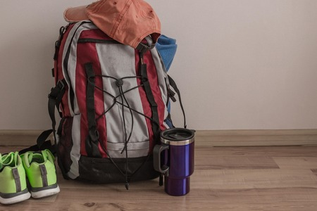 Collected necessary things, tourist equipment. Next to the backpack is a thermo mug and sneakers. Coming soon. Light background, muted tone.