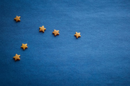 Astrological prediction, horoscope. Small yellow stars on a blue surface. Top view, copy space, vignetting.