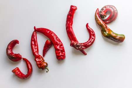 Bright red letters made from hot pepper. Urgent sale, hot offer, discounts. Light background, top view.