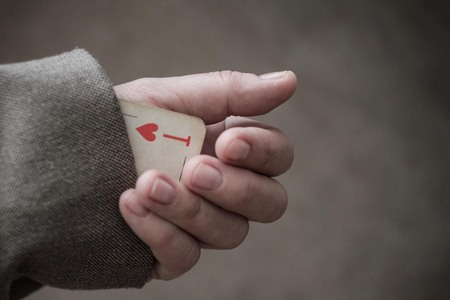 The hand pulls an ace from its sleeve. Concept, symbol. Focus on the playing card. Warm colors, vignetting.