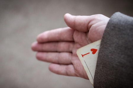 Hidden ace, large playing card, trump card. The game is not by the rules, cheating. Ace in focus, the background is blurred. Vignetting, copy space.