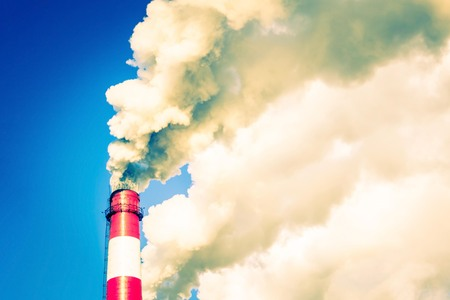 A large factory pipe smokes into the sky. Ecological problems, air pollution. Blue sky. Toning. Imagens