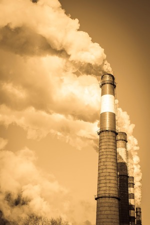 Plant, harmful production, air pollution. Large smoking chimneys against the sky. Toning, vignetting.