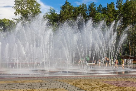 Freshness on a hot summer day, a fountain in the city park. Children run under the water jets. Blue sky, big green trees in the distance. Fun, serenity. Imagens