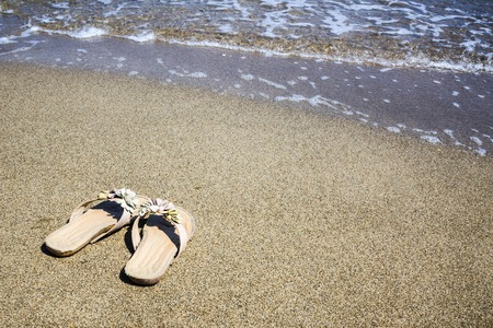 Summer, sun, seashore. Womens slippers on the sand. Leisure, vacation, downshifting. Vignetting Imagens