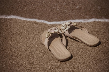 On the sandy beach womens sandals. Sunny summer day, rest, vacation. Vintage toning.