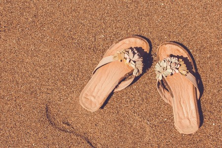 Beach, brown sand, coast. Summer womens shoes, sandals, slippers. Vacation, travel, freedom, pleasure. Copy space, view from above. Imagens