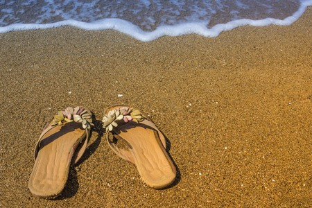 Womens shoes on the beach. Sand, clear water, surf. Bright solar lighting. Toning.