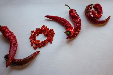 Red letters from hot pepper, the word love. Hot, passionate relationship. Light background, copy space. Imagens