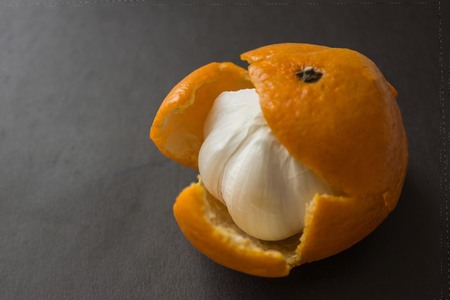 In the orange skin from under the sweet mandarin hides a garlic bulb. Unpleasant surprise, a dirty trick, deceived expectations. Dark background.