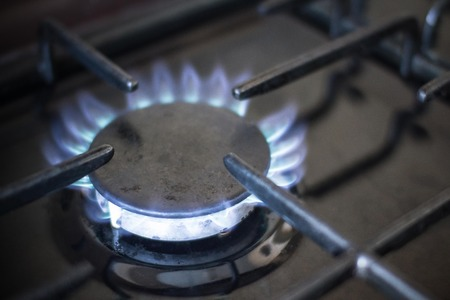 Blue flame burner. The use of natural gas in everyday life. The edges are blurred, dark background.