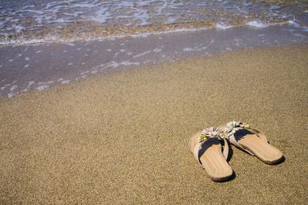 Beach, sea coast, hot summer day. Womens sandals on wet sand. Solar lighting, copy space.