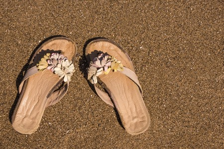 Womens shoes on the beach, the holiday season. Bright sunny day, coast, sand. View from above. Solar lighting, copy space. Imagens