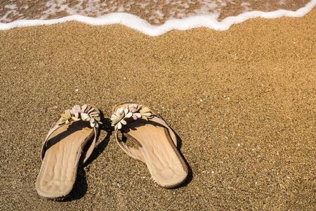 Womens sandals on the beach. Summer, sunny day, no one. Sea coast, beach. Copy space.