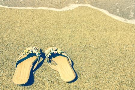 Womens sandals on the sand. Summer, heat, holiday season. Bright solar lighting, toning.