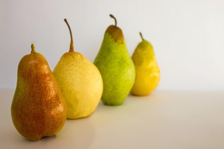 Distinctive appearance, differences of a figure, features. A number of pears of different colors and types. Light background, copy  space, daylight. Imagens