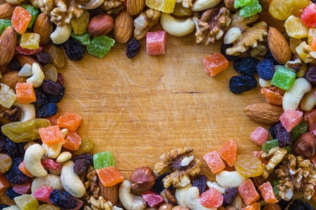 Different nuts and candied fruits on a light wooden background. Home cooking, proper food, vegetarian cuisine. Daylight illumination, top view.